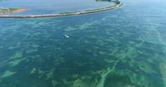 Drone footage of a boat towing an flying inflatable water sled (or flying fish) over the shallow reefs in the south of Serangan island. The camera is turning around a boat with its flying inflatable water sled stopped getting ready for the next ride.