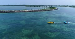 Drone footage of a boat towing an flying inflatable water sled (or flying fish) over the shallow reefs in the south of Serangan island. The camera is following the boat with its flying inflatable water sled from the side going along Serangan reef.