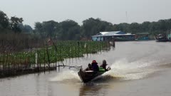 A boat is coming towards the camera on the Kam Flung Poo river passing close to the plantations on its bank.