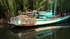 Fishing boat parked along nipa palm trees in a mangrove like part of the Prek Tuek Chhou river north of Kampot.