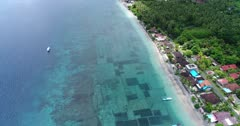 Drone footage of the algae plantation in the shallow reef of the northern part of Nusa Penida. The camera is facing down and is tilting up showing the coast and it's shallow reef.