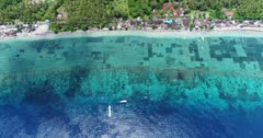 Drone footage of the algae plantation in the shallow reef of the northern part of Nusa Penida. The camera is high facing down showing the turquoise water with the reef, algae plantation, coast and is descending towards a boat tied at the edge of the reef.
