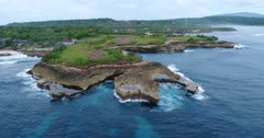Drone footage of the rock formation called devil tears on the western part of Nusa Lembongan with the waves crashing on it. The camera is facing the coast going along it while slowly turning.