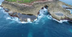 Drone footage of the rock formation called devil tears on the western part of Nusa Lembongan with the waves crashing on it. The camera is facing down at the rocks with the pools of water on them and is going along them while slowly turning.