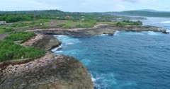 Drone footage of the rock formation called devil tears on the western part of Nusa Lembongan with the waves crashing on it. The camera is facing the coast and slowly going towards the sea while turning.