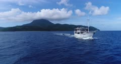 Drone footage of a diving boat towing 2 small inflatable zodiac leaving the shore of Nila island with its perfectly shaped volcano is in the background. The camera is starting low over the water facing the boat and is going away from it while ascending.