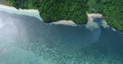 Drone footage of a white sand beach surrounded by tropical vegetation in Nila island, Indonesia. The camera is facing down showing the coast with the paradise looking beach and shallow reef and is descending towards the small secluded bay.
