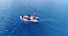 Drone footage of a group of divers ready to jump from an inflatable zodiac which is slowly moving. The camera is slowly following the boat from its side.