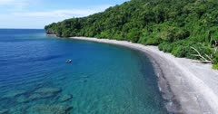 Drone footage of Wetar island with its beach, luxuriant tropical vegetation and turquoise water. The camera is going along the beach and is panning towards the sea and a dive boat floating close by.