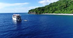 Drone footage of an inflatable zodiac boat leaving a dive boat anchored in front of a beach of Wetar island with its luxuriant tropical vegetation. The camera is facing the stern of the dive boat where the zodiac is leaving from and then is following the zodiac along the beach.
