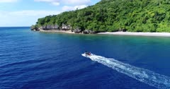 Drone footage of an inflatable zodiac boat following the coastline of Wetar island with its sandy beach and luxuriant tropical vegetation. The camera is behind the zodiac showing it going along the beach and is going towards it while tilting down.