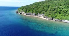 Drone footage of the rocky coastline of Wetar island with its luxuriant tropical vegetation, turquoise water and shallow coral reef. The camera is facing the island with its colorful shallow water and is going towards the rocky shore while descending.