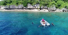 Drone footage of a group of divers floating at the surface next to an inflatable zodiac. The camera is facing the boat with the rocky coast of Wetar island and its luxuriant tropical vegetation behind and is going towards the divers while tilting down.
