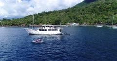 Drone footage of an inflatable zodiac leaving a dive boat and going away from it with Pura island in the background. The camera is turning around the main boat while slowly ascending keeping both boats on the frame.