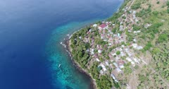 Drone footage of the rocky coast of Pura island with its luxuriant tropical vegetation, shallow coral reef with turquoise water and houses built along its coast. The camera is facing down at the village and the colorful shallow water and is descending straight.