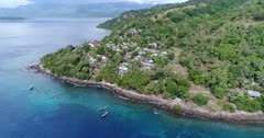 Drone footage of the rocky coast of Pura island with its luxuriant tropical vegetation, shallow coral reef with turquoise water and houses built along its coast. The camera is facing down at the village and the colorful shallow water and is descending while tilting up.