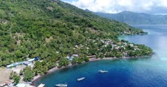 Drone footage of the rocky coast of Pura island with its luxuriant tropical vegetation, shallow coral reef with turquoise water and houses built along its coast. The camera is facing the island and is going sideways over the water while descending.