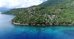 Drone footage of the rocky coast of Pura island with its luxuriant tropical vegetation, shallow coral reef with turquoise water and houses built along its coast. The camera is facing the island and is going sideways along the coast ending up in a bay where a dive boat is anchored.