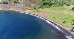 Drone footage of a black sand beach in the south of Pantar island, some grass and bush trees are growing along it. The camera is going away from the beach while ascending above the water.