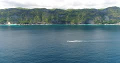 Drone footage of a small boat driving along the west coast of Nusa Penida with its beautiful cliffs and turquoise water. The camera is starting far away over the water facing the coast and is going towards the boat.