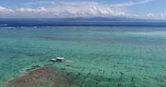 Drone footage of a small boat driving over shallow reef and turquoise water in the north of Nusa Lembongan. The camera is facing the sea and is slowly following the boat.