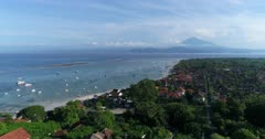 Drone footage of the north part of Nusa Lembongan with its white sand beach, shallow water and reef and the Agung volcano in the background. The camera is facing Bali island and is going towards it while ascending, going over Lembongan beach.