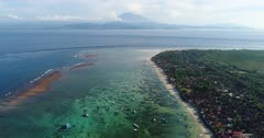 Drone footage of the north part of Nusa Lembongan with its white sand beach, shallow water and reef and the Agung volcano in the background. The camera is facing Bali island and is going away from it, going over Lembongan beach.