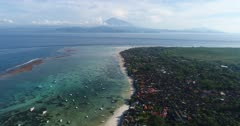 Drone footage of the north part of Nusa Lembongan with its white sand beach, shallow water and reef and the Agung volcano in the background. The camera is facing Bali island with its volcano and is going over Lembongan island while descending.