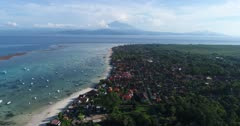 Drone footage of the north part of Nusa Lembongan with its white sand beach, shallow water and reef and the Agung volcano in the background. The camera is facing Bali island with its volcano and is going over Lembongan island while descending and panning.