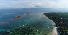 Drone footage of the north part of Nusa Lembongan with its white sand beach, shallow water and reef and the Agung volcano in the background. The camera is facing Bali island and is going away from it, going over Lembongan island.