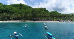 Drone footage of crystal bay in the north of Nusa Penida with palm trees on the beach, turquoise water and shallow reef. The camera is facing the beach and is going away from it over the colorful water showing the many boats floating over the shallow reef.
