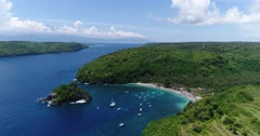 Drone footage of crystal bay in the north of Nusa Penida with palm trees on the beach, turquoise water and shallow reef. The camera is facing the bay and is going away from it along the coast. The Agung volcano of Bali is in the background surrounded by clouds.