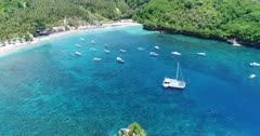 Drone footage of crystal bay in the north of Nusa Penida with palm trees on the beach, turquoise water and shallow reef. The camera is facing the beach and is going away from it over the colorful water while ascending with the many boats floating over the shallow reef and ending showing the whole bay.