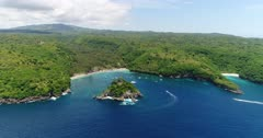 Drone footage of crystal bay in the north of Nusa Penida with palm trees on the beach, turquoise water and shallow reef. The camera is showing the whole bay and is going towards the beach while descending.