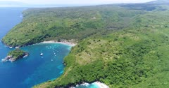Drone footage of crystal bay in the north of Nusa Penida with palm trees on the beach, turquoise water and shallow reef. The camera is showing the whole bay from the side and is panning while going away unveiling the small beach next to it.