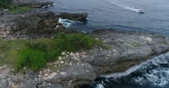 Drone footage of the west part of Nusa Ceningan with its rock formations and waves crashing on it. The camera is facing down at the rocks and is following the coast, a boat is passing by.