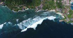 Drone footage of waves crashing on the shallow reef of the west part of Nusa Ceningan. The camera is facing down at birdview angle high over the waves and is static.