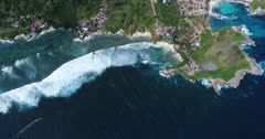 Drone footage of waves crashing on the shallow reef of the west part of Nusa Ceningan. The camera is facing down at birdview angle high over the waves and is going along the coast.