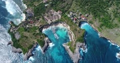Drone footage of waves crashing on the shallow reef of the west part of Nusa Ceningan. The camera is facing down at birdview angle over a bay with colorful water and is going along the coast while turning.