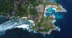 Drone footage of waves crashing on the shallow reef of the west part of Nusa Ceningan. The camera is facing down at birdview angle over a bay with colorful water and is going along the coast.