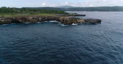 Drone footage of waves crashing on the rocky coastline of the western part of Nusa Ceningan. The camera is starting over the sea and is going towards the island passing on top of the rocks.