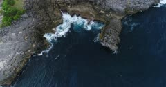 Drone footage of waves crashing on the rocky coastline of the west part of Nusa Ceningan. The camera is facing down at the rocks slightly going towards them.