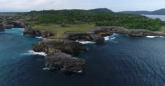 Drone footage of waves crashing on the rocky coastline of the west part of Nusa Ceningan. The camera is facing the island going sideways while panning ending up over the rocks.