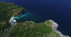 Drone footage of secret beach in the south-west part of Nusa Ceningan. The camera is facing down at the bay with its colorful water and is slowly panning while descending.