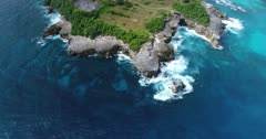 Drone footage of waves crashing on the rocky coastline of the west part of Nusa Ceningan. The camera is facing down at the rocks and is going along the coast while turning.
