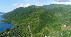 Drone footage of the hills of Alor island with its luxuriant tropical vegetation and a small village built along its coast. The camera is starting showing the hills of the island and is going sideways while turning and descending ending up facing the beach and the village nearby.