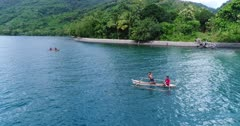 Drone footage of kids paddling on tiny local boats close to a beach of Alor island with its luxuriant tropical vegetation. The camera is facing the beach and is slowly panning while the kids are waving at the camera and paddling around in their small wooden boats.