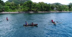 Drone footage of kids paddling on tiny local boats close to a beach of Alor island with its luxuriant tropical vegetation. The camera is facing the beach and is panning following the kids waving and paddling around in their small wooden boats.