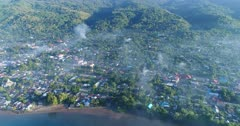Drone footage of Kalabahi city in Alor island under an early morning fog covering the houses along the water. The camera is facing the island and is going away from it over the water while tilting up showing the hills covered in tropical vegetation in the background.