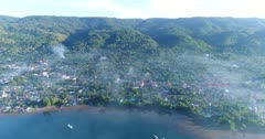 Drone footage of Kalabahi city in Alor island under an early morning fog covering the houses along the water. The camera is facing the island with the houses and the hills covered in tropical vegetation behind and is panning towards the sun.
